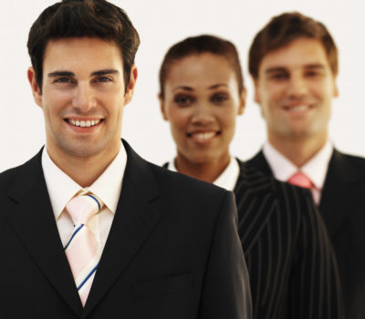 Front view portrait of three business executives smiling --- Image by © Royalty-Free/Corbis